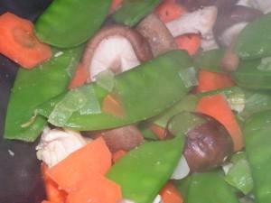 Dampfende Karotten, Zuckerschoten, Shiitake-Pilze und Pute im Wok